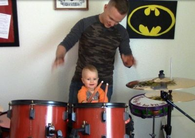 Small child playing on a drumset